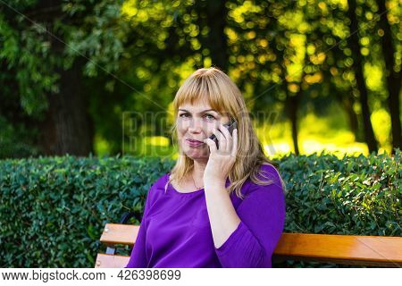 Defocus Caucasian Blond Woman Talking, Speaking On The Phone Outside, Outdoor. 40s Years Old Woman I
