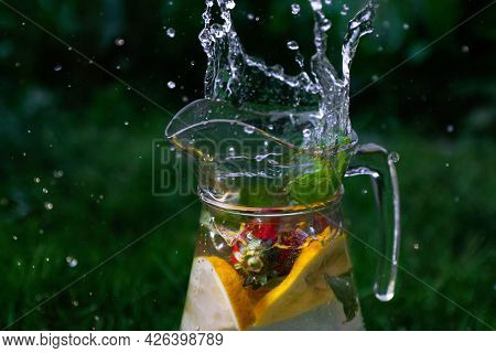 Defocus Splash Water Bubbles In Glass Jug Of Lemonade With Slice Lemon, Strawberry And Mint On Natur