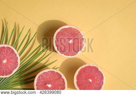Summer Still Life With Cut Grapefruits Into Half On Yellow Background. Top View With Copy Space.