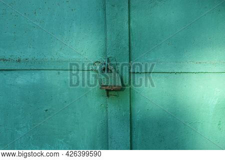 One Big Old Iron Green Lock Hanging On A Metal Door