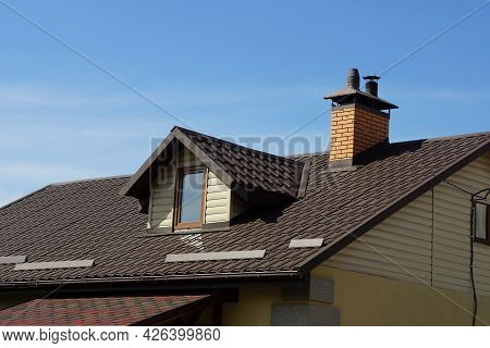 Part Of A Private House From An Attic With A Window Under A Brown Tiled Roof With A Brick Chimney On