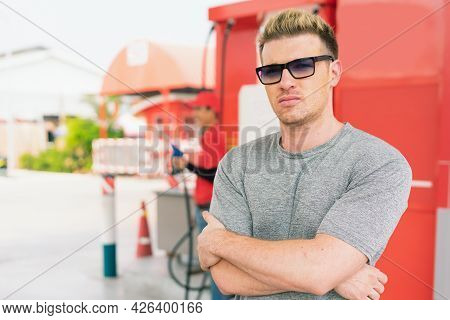 White Caucasian Standing With Smart In Front Of Fuel Nozzle Tank After Filling High Energy Power Fue