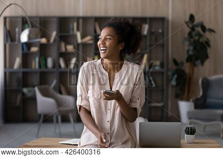 Overjoyed African American Woman Distracted From Phone, Looking To Aside