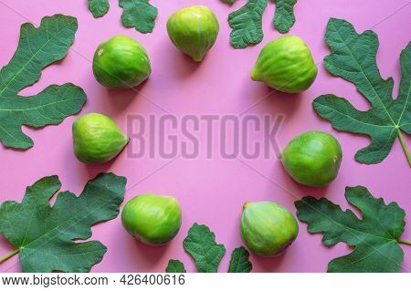 Ripe Fig Fruit And Green Leaves Of A Fig Tree On Pink Paper Background.  Flat Lay. Copy Space