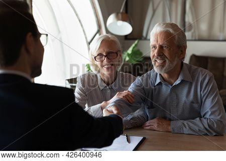 Happy Grateful Elderly Couple Of Clients Thanking Real Estate Agent