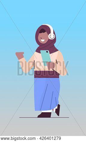 Arab Schoolgirl Using Smartphone And Listening To Music In Headphones Arabic Girl With Gadget Vertic