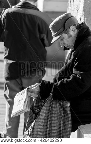 Timisoara, Romania - March 14, 2016: Man Reading A Newspaper On The Street. Real People. Black And W