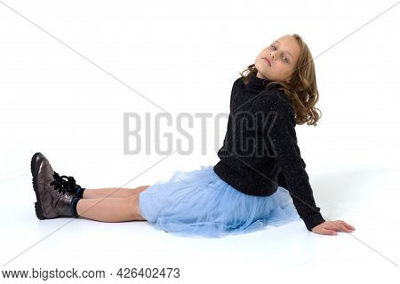 Girl Sitting On Floor Leaning Back On Her Hands. Preteen Girl In Knitted Pullover And Light Blue Ski