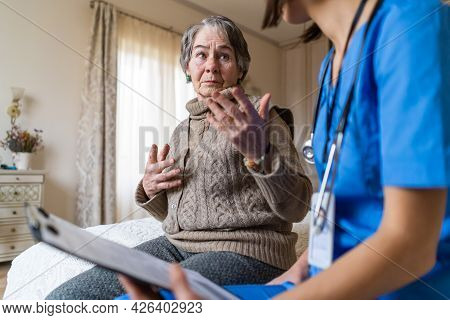 A Young Nurse Takes Care Of An Elderly 80-year-old Woman At Home, Explains The Methods Of Treatment.