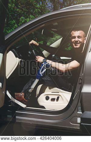 A Man On A Prosthetic Leg Sits In A Car. Dressed In Black Jeans And A T-shirt