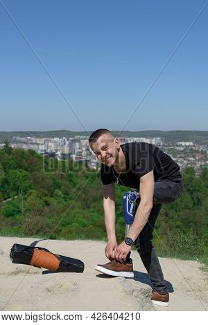 A Man On A Prosthetic Leg Travels The Mountains. Dressed In Black Jeans And A T-shirt.