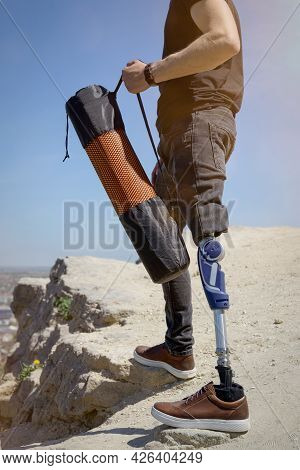 A Man On A Prosthetic Leg Travels The Mountains. Dressed In Black Jeans And A T-shirt, He Carrying M