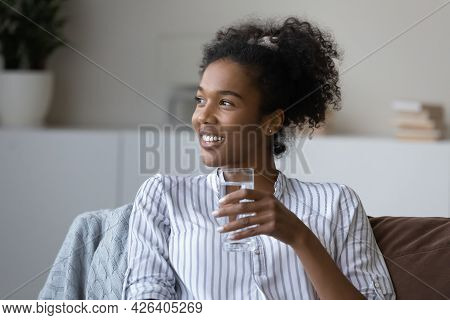 Smiling Dreamy African American Woman Holding Glass Of Pure Water