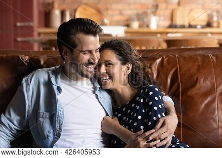 Happy Young Millennial Married Couple Resting And Hugging On Sofa
