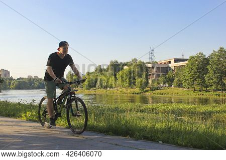 A Guy Rides A Bike In The Park. Young Fit Man During A Bike Ride On A Sunny Day