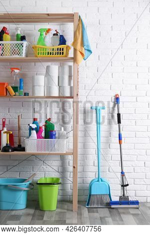 Shelving Unit With Detergents, Cleaning Tools And Toilet Paper Near White Brick Wall Indoors