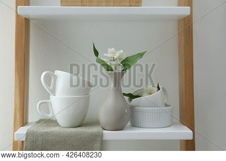 Beautiful Jasmine Flowers And Tableware On Shelving Unit In Kitchen
