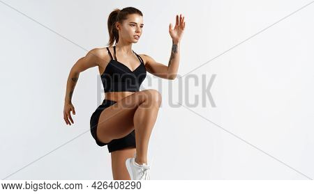 Image Of Sporty Young Female Athlete, Doing Leg Stretching Exercises, Lifting Legs, Dynamic Movement