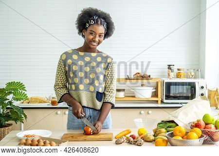Healthy Eating, African American Happy Girl  Making Dinner And Chopping  Tomatoes On Cutting Board W