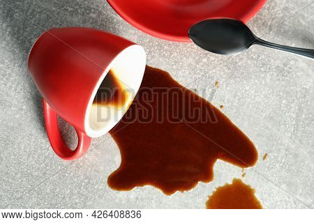 Cup, Saucer And Spoon Near Spilled Coffee On Grey Table