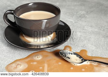 Cup, Saucer And Spoon Near Spilled Coffee On Grey Table, Closeup
