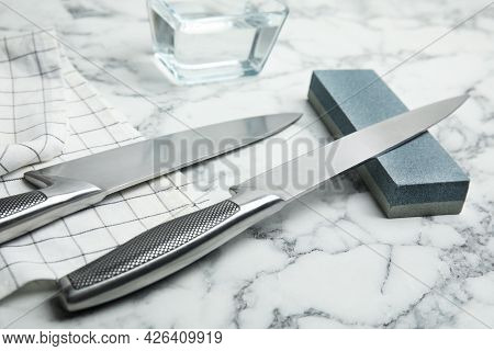 Sharpening Stone And Knives On White Marble Table, Closeup