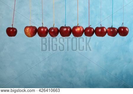 Ripe Red Apples Hanging On Light Blue Background, Space For Text