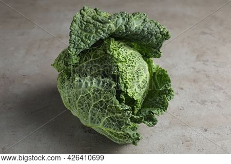 Fresh Ripe Savoy Cabbage With Water Drops On Grey Table