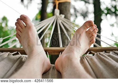 Close-up Of Male Feet On Hammock. Man Resting On Hammock At Summer Day.