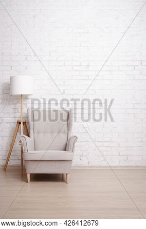Armchair And Lamp With Copy Space Over Brick Wall Background