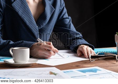 Corporate Consultant Analyze Financial Diagram. Close Up Woman Hand With Pen And Coffee Cup On Woode