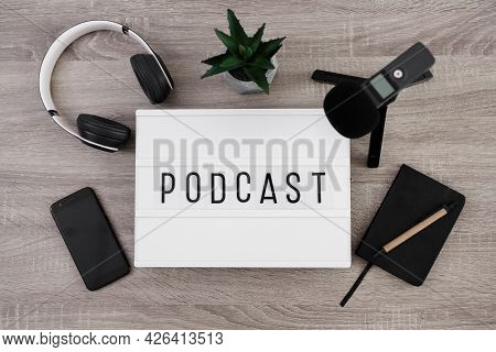 Podcast Concept - White Lightbox With Podcast Word On The Table With Microphone, Headphones, Smartph