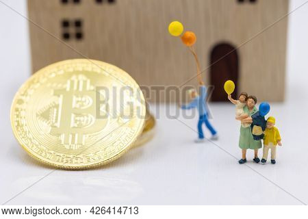 Miniature People Standing With Gold Bitcoin And House.  Concept Of Business, Money, Technology, Cryp