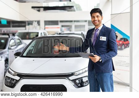 Handsome Young Salesman Standing At The Dealership, Showing Car