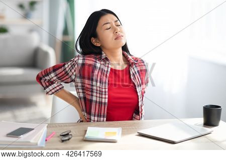 Beautiful Young Asian Woman Suffering From Backache While Working In Home Office