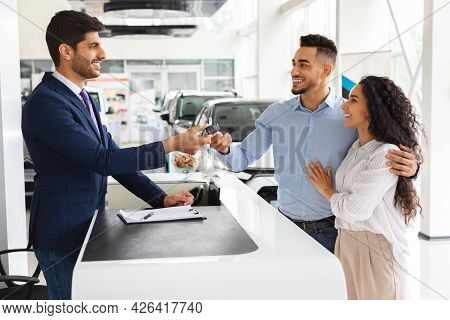 Excited Middle-eastern Couple Buying Car In Huge Showroom