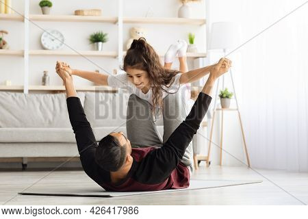Adorable Little Girl Exercising With Her Daddy At Home
