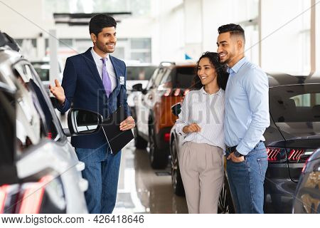 Beautiful Middle-eastern Couple Buying Car In Brand New Showroom