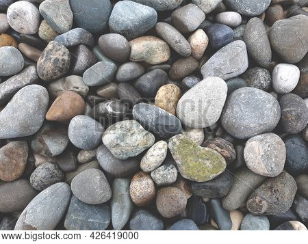 Background Of Multicolored Pebbles, One Green Pebbles Similar To Heart In The Right