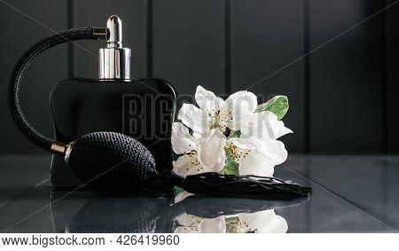 Black Bottle Of Eau De Toilette Or Perfume With Long Tassel Spray Pomp Stands On Dark Background On