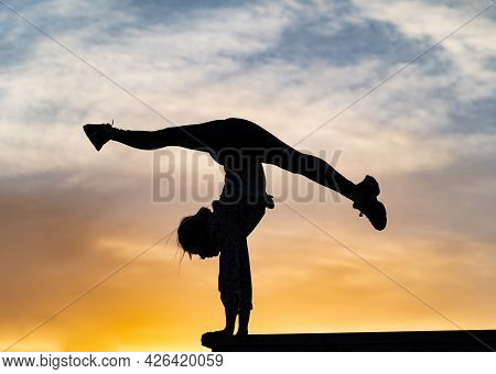 Silhouette Of Flexible Woman Gymnast Doing Handstand On The Dramatic Sunset. Concept Of Individualit