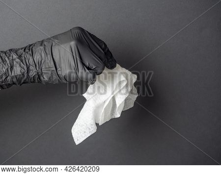 A Hand Wearing A Black Latex Glove Holds A White Rag On A Black Background