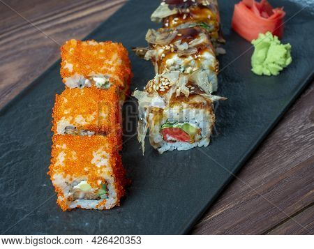 Side View Of Juicy Delicious Rolls Decorated With Caviar. Japanese Cuisine, Black Plate, Close Up