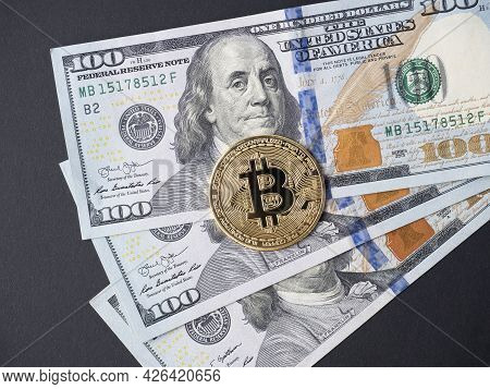 Yellow Bitcoin Lies On Hundred-dollar Bills. The Concept Of Cryptocurrency, Investment, Income. Top