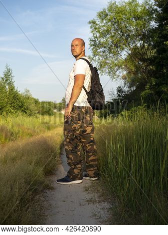 A Middle-aged Man With A Black Backpack Is Standing On A Forest Path At Sunset. The Concept Of Trave