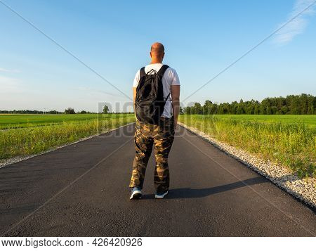 A Middle-aged Man Is Standing On An Asphalt Road With A Black Backpack On His Back. Rear View. The C