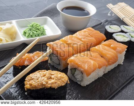 A Variety Of Japanese Rolls And Sushi On A Textured Plate. Side View. Bamboo Sticks Of Ginger And Sa