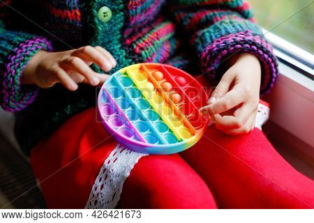 Little Blonde Preschool Girl Playing With New Trend Sensory Toy - Rainbow Pop It. Antistress Toy For