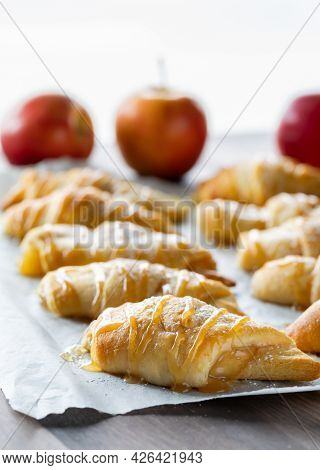 Apple Filled Crescent Rolls On A Parchment Lined Baking Sheet With Light Coming From Behind.
