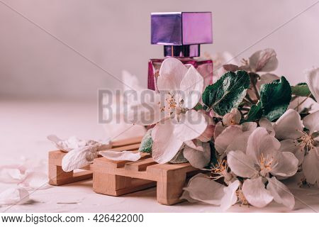Lilac Glass Bottle Of Eau De Toilette Or Perfume With Square Cap On Wooden Podium In Form Of Pallet